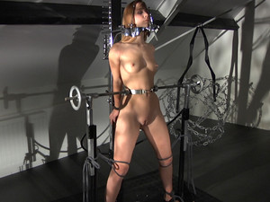 Dominated blonde fixed in metal device for pain and pleasure