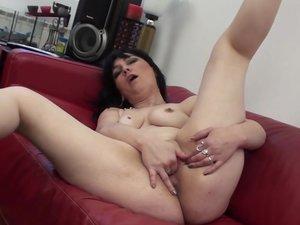 Horny mature slut masturbating on a couch
