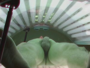 Handsome young man filmed secret camera in public solarium